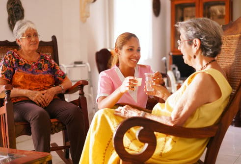 caregiver giving medicine and water to senior woman