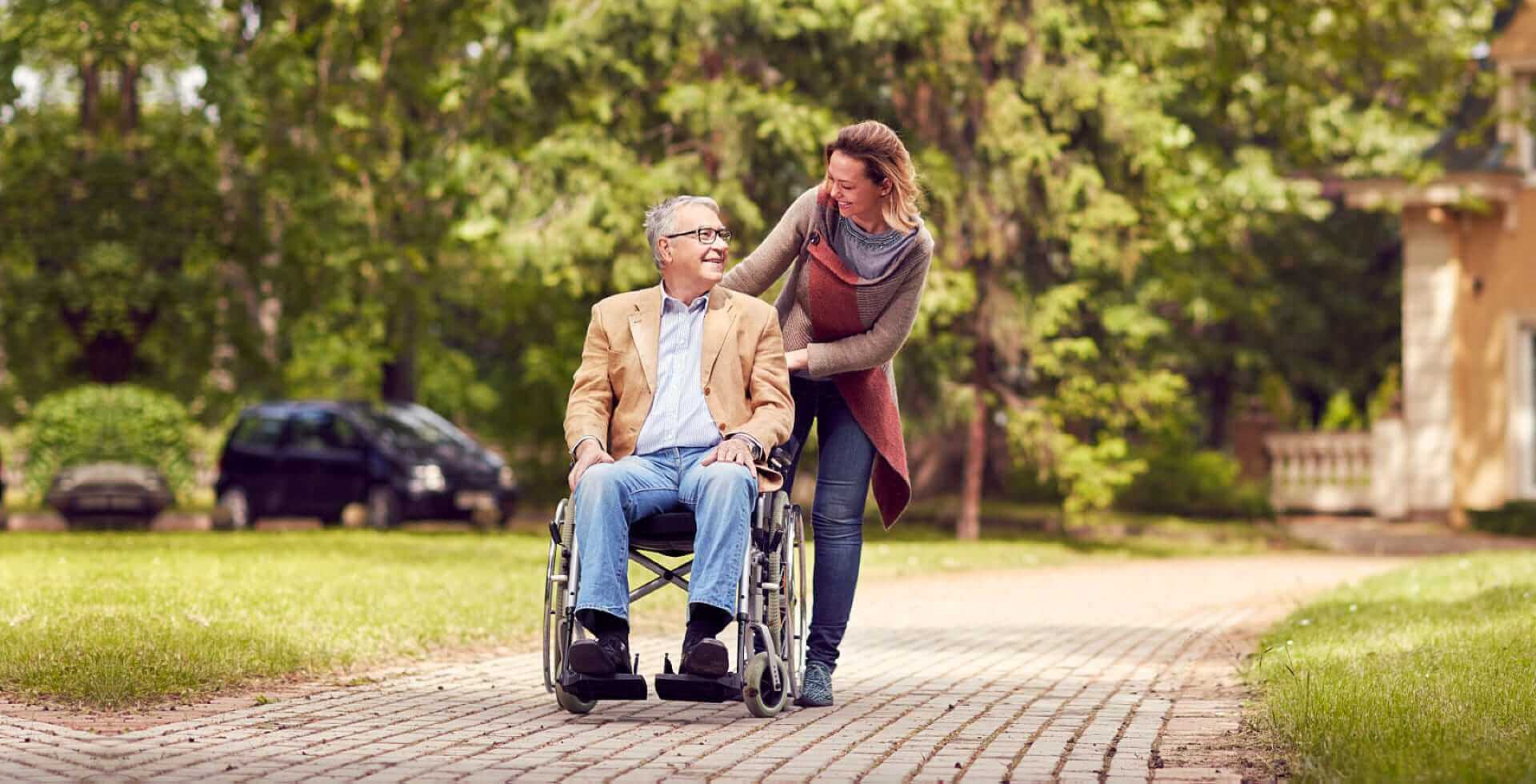 caregiver and senior man in a wheelchair smiling each other
