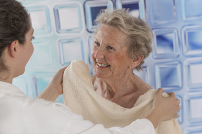 caregiver assisting elder woman for shower