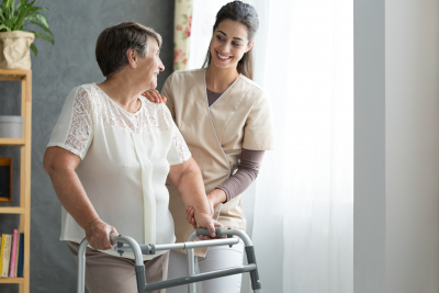 caregiver assisting elder woman to walk